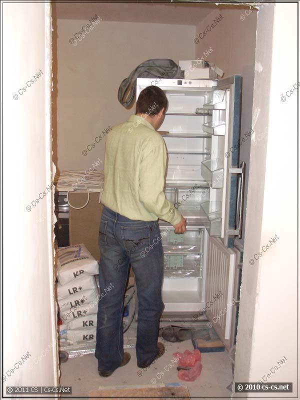 Дохтур выгружает свой размороженный холодильник