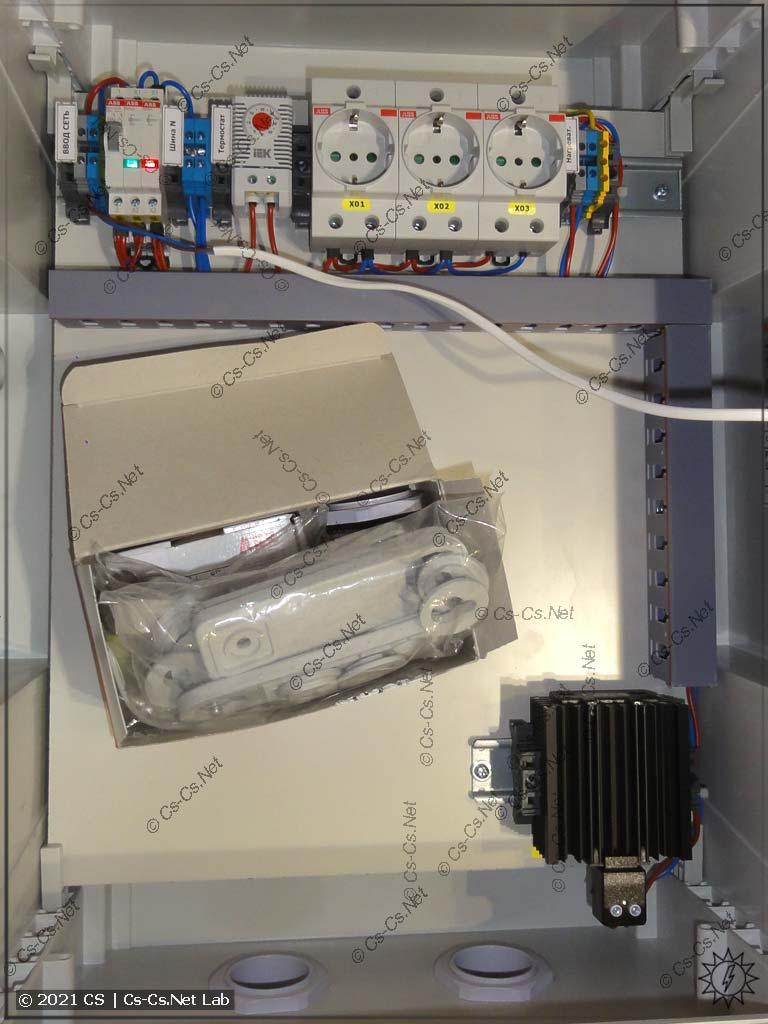 Вид на монтаж электрики, термостата и нагревателя в шкафу ABB Gemini для улицы