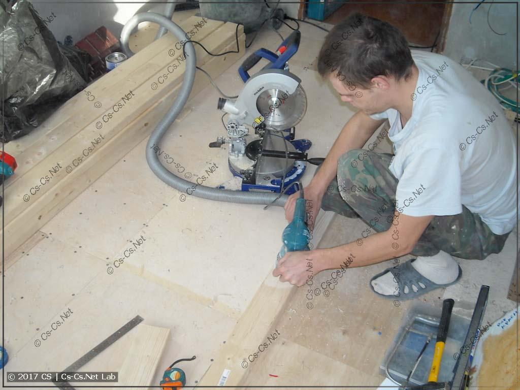 Напарник помогает мне резать доски для потолка