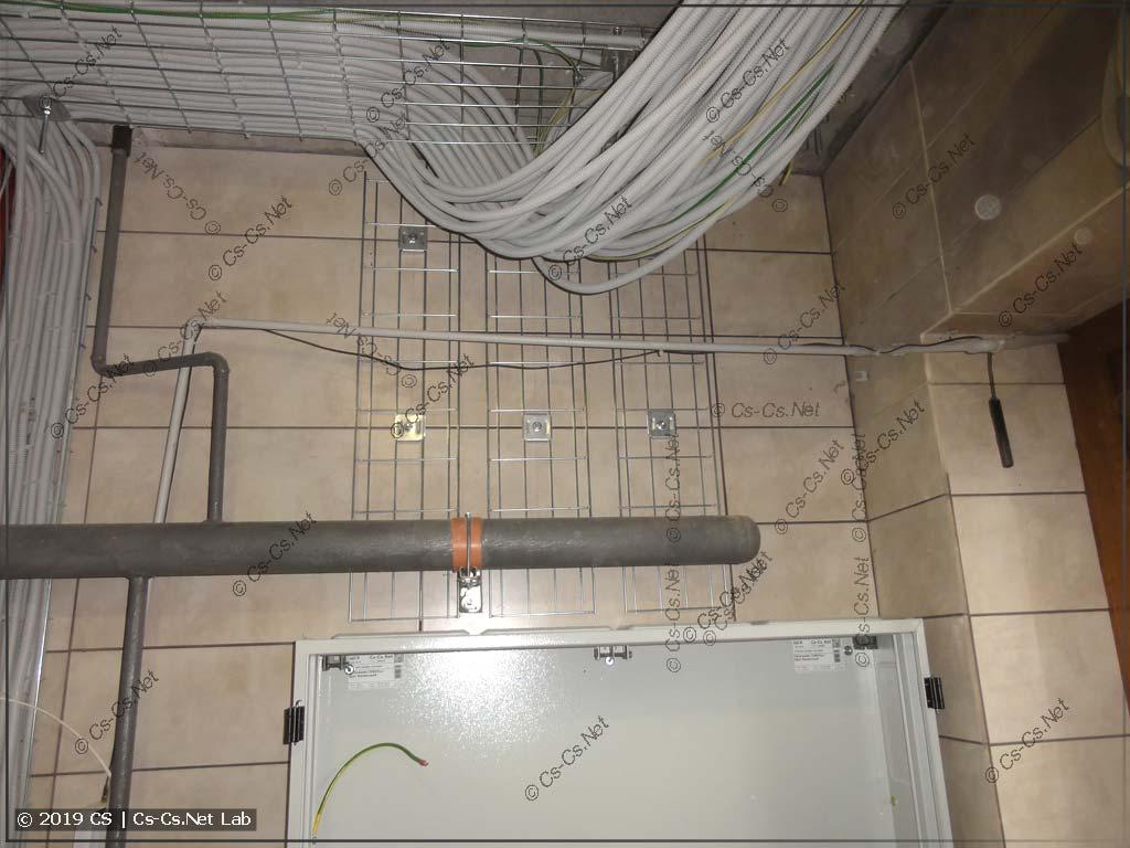Щит повешен на стену и к нему подведены лотки для опусков кабелей
